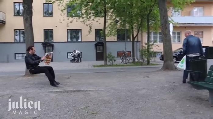 Парень сидит на невидимом стуле и читает газету