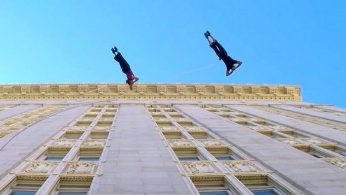Пара танцует на стене высотного здания